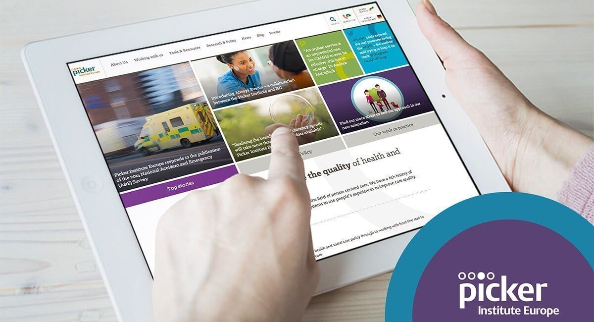 An image presenting two hands holding the tablet with the Picker website.
