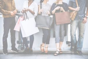 An image presenting various people standing near to wall, holding their shopping bags.