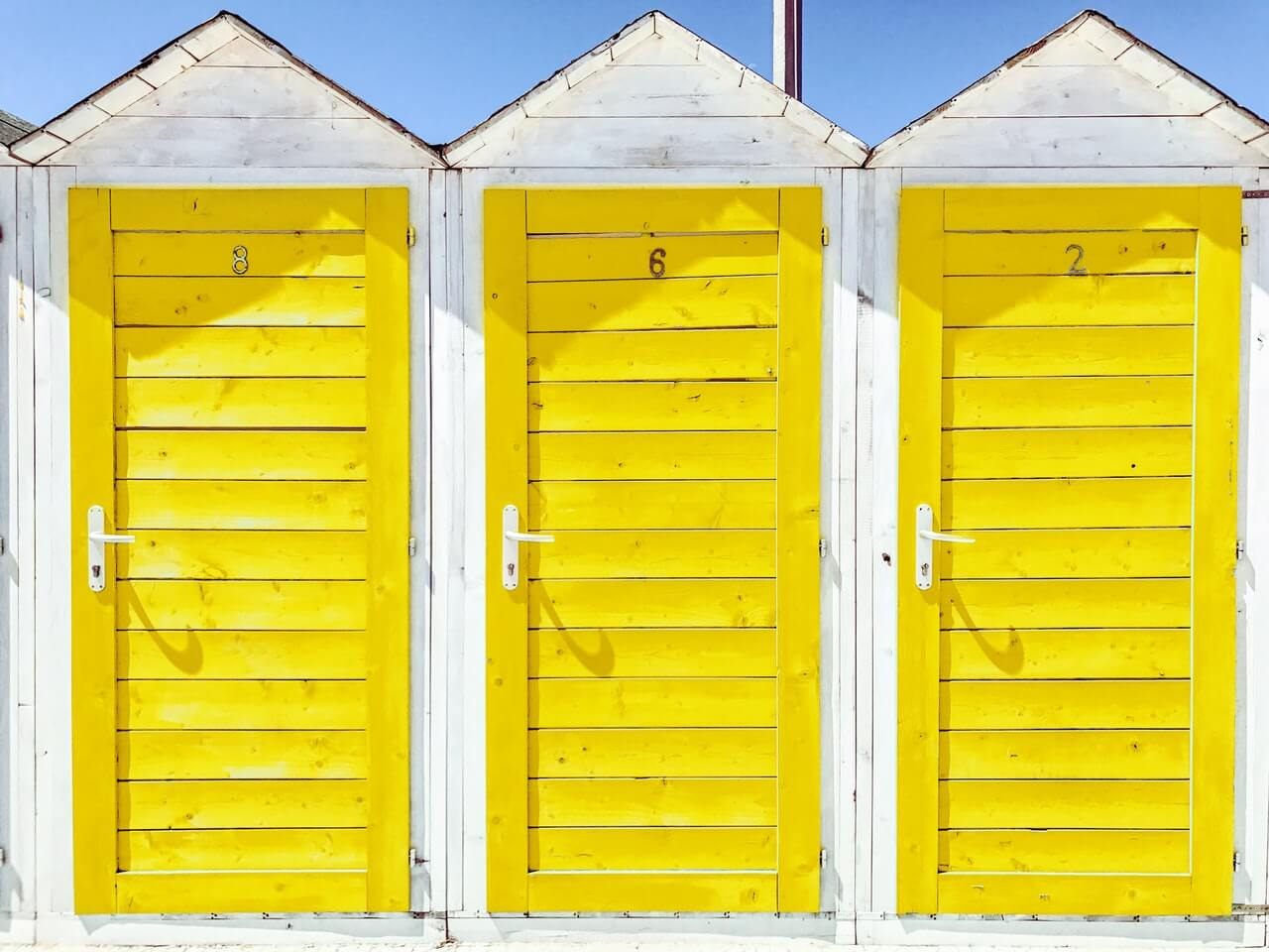Three wooden doors painted in yellow. Each doors present different NetSuite partner.